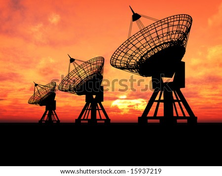 Three satelite dishes over sunset - stock photo