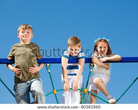 Three school aged friends climbing the net - stock photo