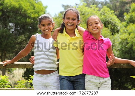 Three school girl friends outdoors together in the park