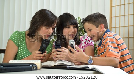 Three school kids playing around with their cell phones instead of studying. - stock photo
