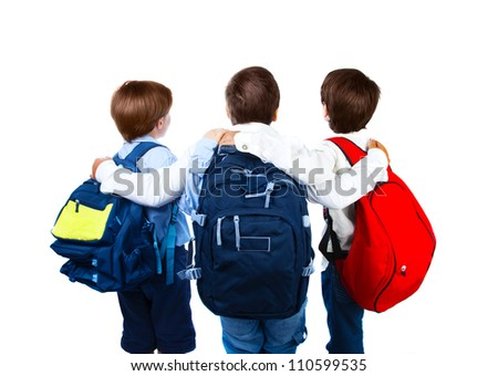 Three schoolboys isolated on white background, rear view of three teenager with colorful backpacks, best friends standing and hugs in studio, back to school, education concept - stock photo
