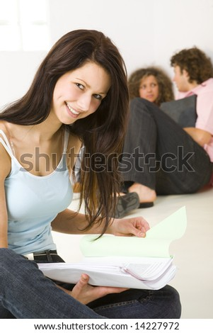 Three schoolmate holding a notebooks and sitting on the floor. A boy talking with girl in pink shirt. A girl in blue shirt smiling and looking at camera. Focused on girl in blue shirt. - stock photo