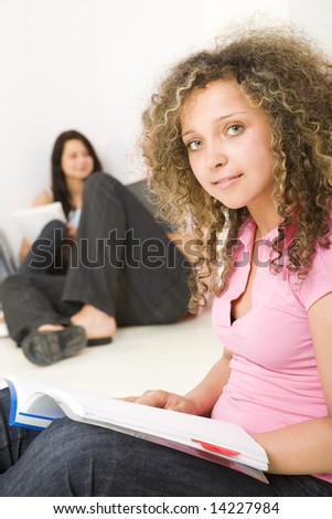 Three schoolmate holding a notebooks and sitting on the floor. A girl in pink shirt smiling and looking at camera. A boy talking with second girl . Focused on girl in pink shirt. - stock photo