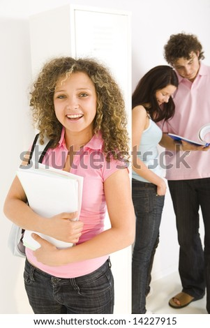 Three schoolmate standing at hollway. A boy showing to girl in blue shirt a notes. Girl in ping shirt holding notebooks and looking at camera. Focused on girl in pink shirt. - stock photo