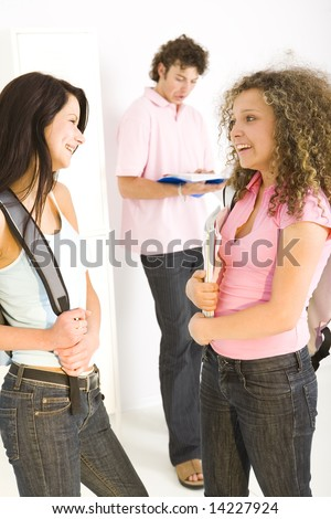 Three schoolmate standing at hollway. A boy standing near shool locker and reading notes. Two happy girls talking with themselves. Focused on the girls. - stock photo