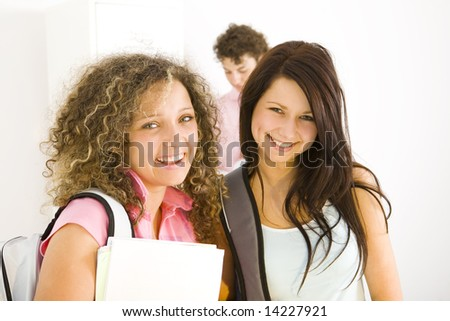 Three schoolmate standing at hollway. Two girls smiling and looking at camera. Focused on the girls. Front view. - stock photo