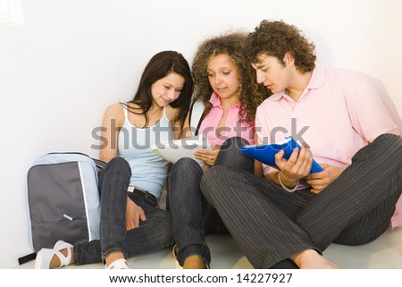 Three schoolmates sitting on the floor and reading notes. Front view.