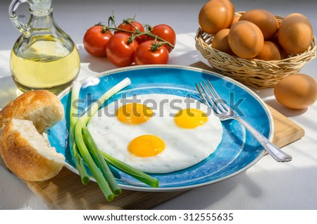 Three scrambled eggs on a blue plate with green onion, fork, bread, a basket eggs, tomatoes, and a bottle of olive oil.
