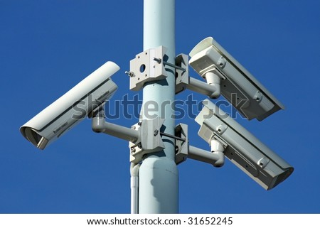 three security cameras on blue background - stock photo