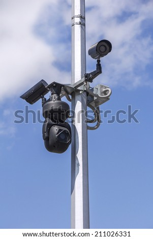 Three Security cameras on blue sky background  - stock photo