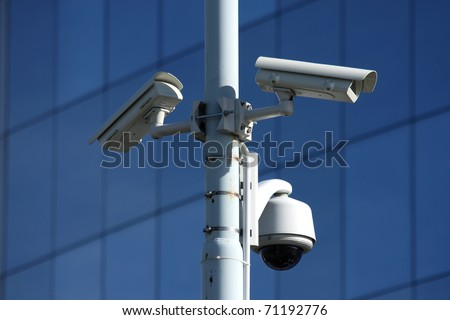 three security cameras on front of glass building - stock photo