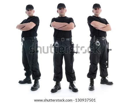 Three security men wearing black uniform equipped with police clubs and handcuffs standing confidently with arms crossed from left to right, shot on white - stock photo