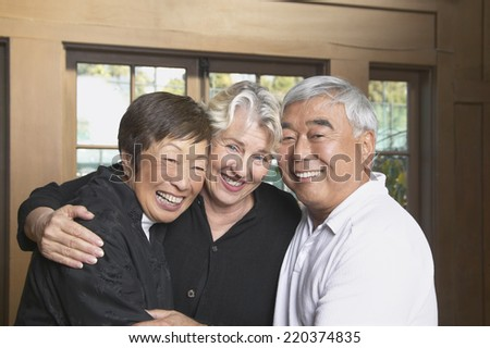 Three senior friends hugging and smiling - stock photo
