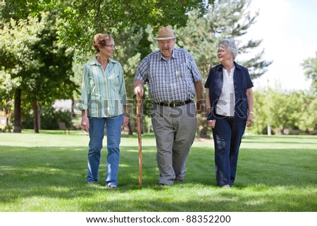 Three senior friends walking in park during summer - stock photo
