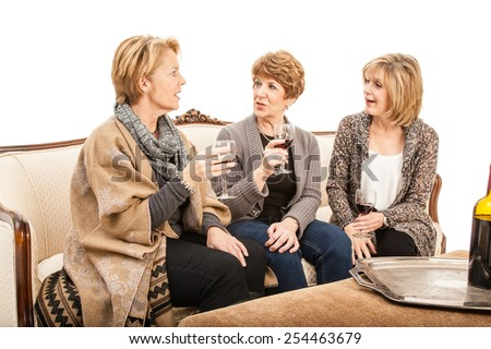 Three senior women sitting on a couch drinking wine