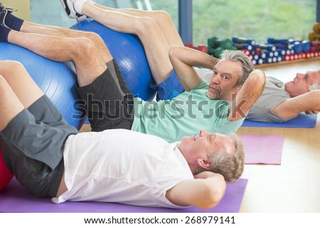 Three seniors using gym equipment for sit-ups at the gym - stock photo