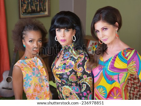 Three serious beautiful women in 1960s fashion - stock photo