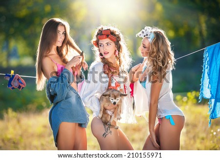 Three sexy women with provocative outfits putting clothes to dry in sun. Sensual young females laughing putting out the washing to dry in sunny day. Perfect body housewives with a dog, shot in forest - stock photo