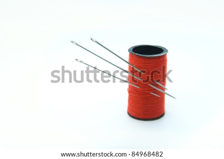 Three sharp metal needles in the bobbin with red thread