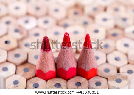 three sharpened red pencil among many ones - stock photo
