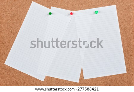 Three sheets of ruled note paper pinned on cork board. - stock photo