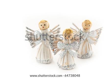 three shining christmas angel figurines on white background