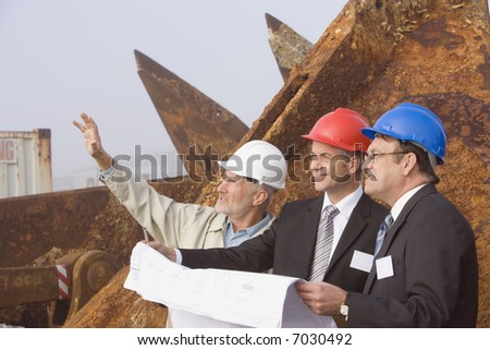 Three shipping inspection engineer taking notes and planning in front of a large rusted anchor in the early morning fog - stock photo