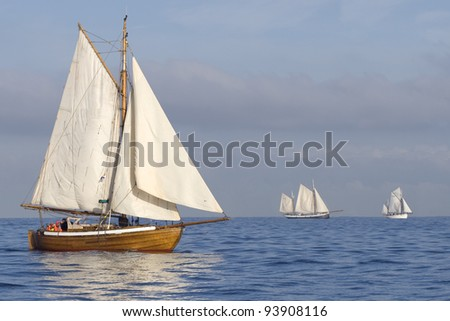 Three ships with white sails in the calm sea - stock photo