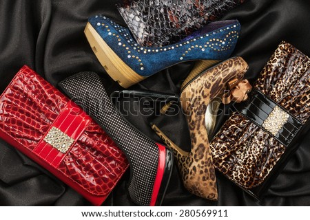 Three shoes and purses are on the black silk, as background - stock photo