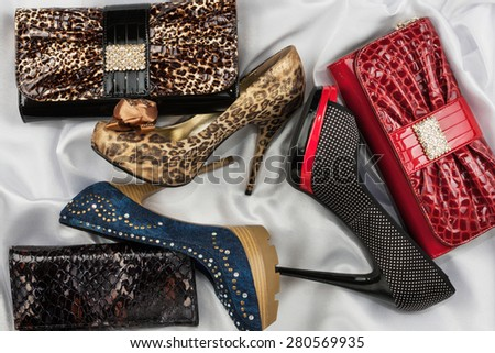 Three shoes and purses are on the white silk, as background - stock photo