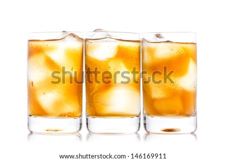 Three shot glass of drink and ice isolated on white