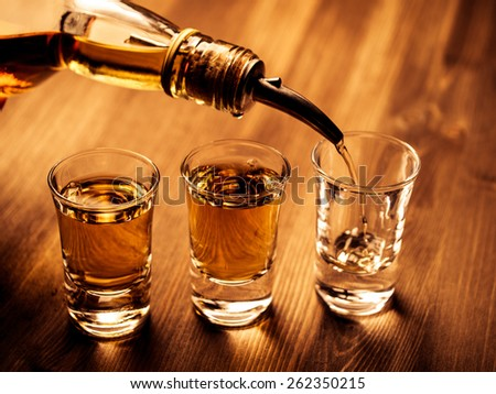Three shot glasses being filled with a drink - stock photo