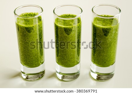 Three shot glasses filled with fresh spinach and kale detox health smoothie in a line - stock photo