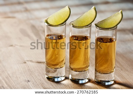 Three shots of tequila and lime wedges