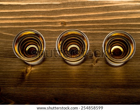 Three shots of whisky on a bar top - stock photo
