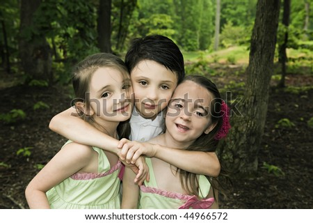 Three siblings hugging in an outdoor setting. - stock photo
