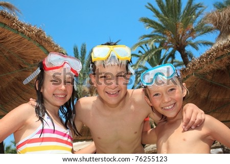 Three siblings in bathing suits, snorkels and diving masks. - stock photo