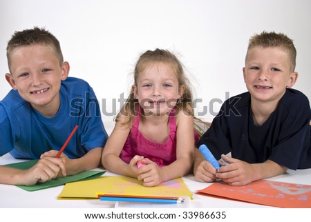Three siblings lying on the floor coloring on bright colored paper.