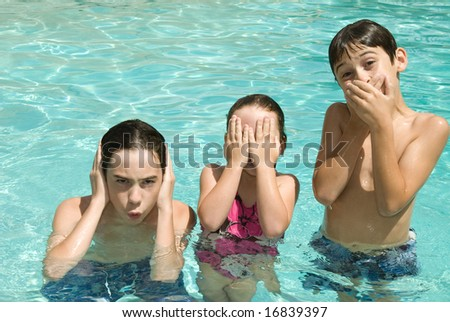 Three siblings pose for the hear no evil, see no evil and speak no evil concept while cooling off in a swimming pool.