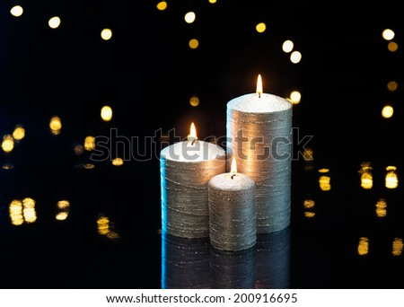 Three silver candles in front of dark background - stock photo