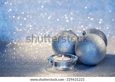 Three silver Christmas balls and candle on a blur background. Selective focus.