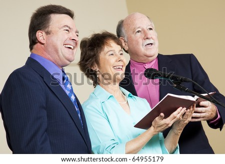 Three singers performing from the church hymnal. - stock photo