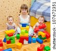 Three sisters - a preschooler girl and two twins baby toy building of the blocks. Older sister teaching younger. - stock photo