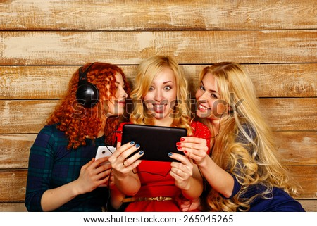 Three sisters, blond and red, listening to music on headphones. Girls having fun and are surprised, looking at the screen the tablet PC, making happy selfie. Sisters sitting in the bedroom. - stock photo