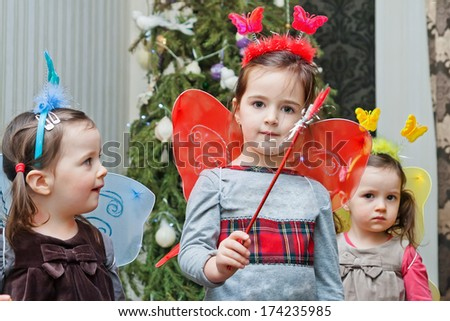 Three sisters in butterfly costumes with magic wands - stock photo