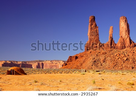 Three Sisters mesa in Monument Valley and traditional indian dwelling with tourist looking inside.
