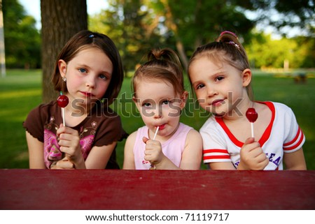 Three sisters sitting at a picnic table in a park eating lollipop suckers - stock photo