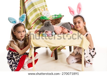 Three sisters with Easter bunny ears and eggs - stock photo