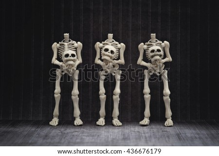 Three skeletons holding their own head with black background - stock photo