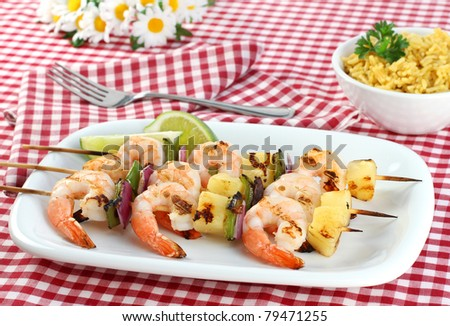 Three skewers of barbecued shrimp, peppers, onion and pineapple.  Red checked picnic tablecloth, daisies, and a side of rice. - stock photo